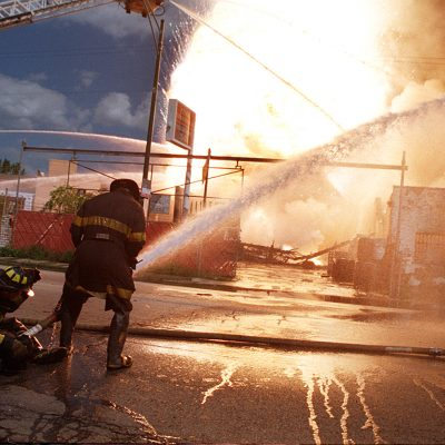 Firefighters battle a hazardous material fire at a recycling company on Grand Ave. & Artesian Ave. in Chicago. The blaze was especially difficult since it involved magnesium, a metal commonly used in flares & fireworks which can become more volatile when wet, creating explosions & floating embers than burn through clothes & skin. The blaze and resulting explosions leveled the building and damaged several area homes. Photo by Vincent D. Johnson,  September 1st, 1998.