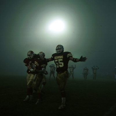 Morris High School football players celebrate after the final seconds of their state playoff semi-final victory of Metamora. A change in the weather brought about a thick fog starting at halftime making it difficult to see the even the other sideline. Photo by Vincent D. Johnson/for IHSFW.com Nov., 2001.