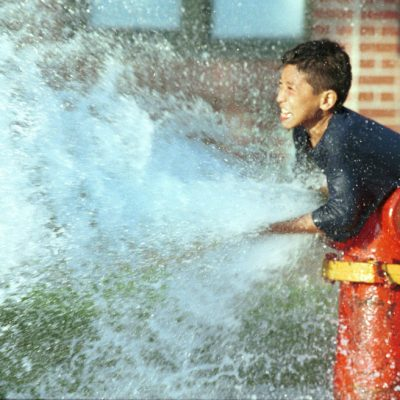 A young boy in the Logan Square neighborhood of Chicago, diverts water being released from a fire hydrant during a sweltering heat wave in the summer of 1998.